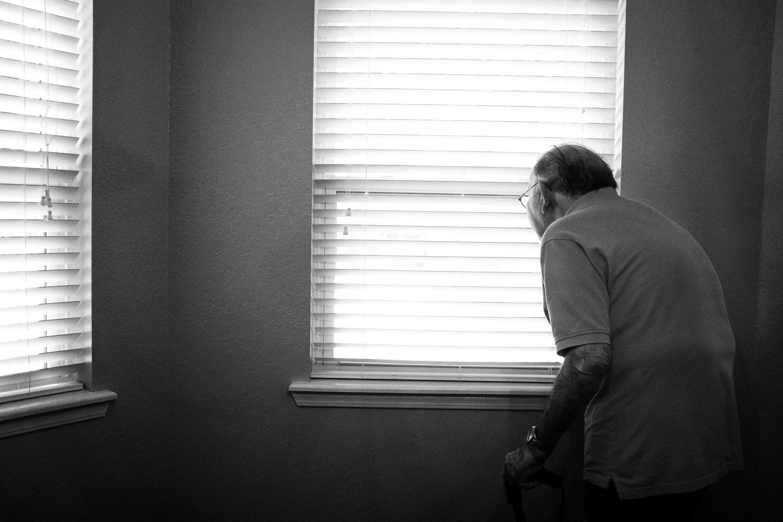 Persona anziana che guarda fuori dalla finestra